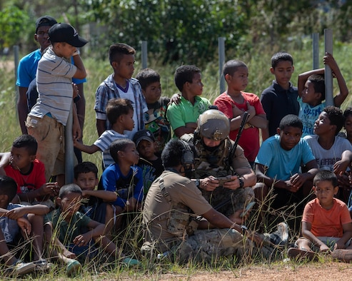 Honduran children in shorts and tee-shirts huddle around two Special Tactics Operators, one sitting on the ground, the other squatting and tapping into a tablet.