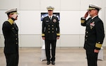 Rear Adm. Kevin Byrne, commander, NAVSEA Warfare Centers (center) looks on as Capt. Eric C. Correll (left) relieves Capt. Scott H. Kraft (right) as commanding officer of NSWC Indian Head Division on Dec. 16, during a change of command ceremony at the College of Southern Maryland's Velocity Center in Indian Head, Maryland.