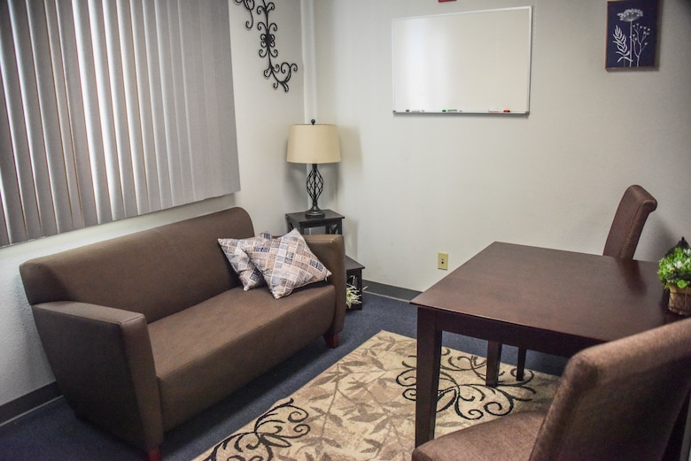 A picture of a small room with brand new furniture and carpet.