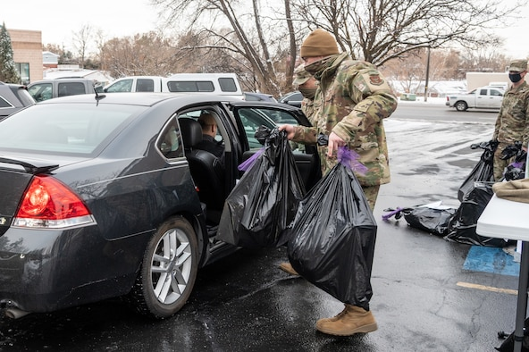 Senior Airman Ben Little, 419th Fighter Wing, loads bags of wrapped gifts into a volunteer's car at Utah Foster Care Foundation in Ogden, Utah, Dec. 17, 2020, as part of a volunteer effort called Santa Brigade