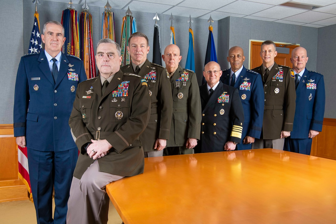 Eight men wearing military uniforms gather around a table; a number of flags are in the background.