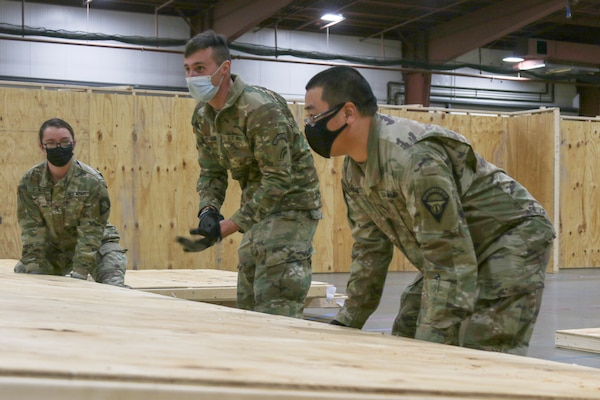 Soldiers and Airmen assigned to the Vermont National Guard's COVID-19 response reconstruct the Alternate Healthcare Facility at the Champlain Valley Fairgrounds in Essex Junction, Vermont, Nov. 19, 2020. The AHF was originally constructed in April, but was disassembled in July after seeing little use. The Vermont National Guard is reusing the materials from the earlier project to construct this smaller facility, which will remain locked until the the Vermont Department of Health determines it is needed. It can accommodate up to 200 patients if needed.