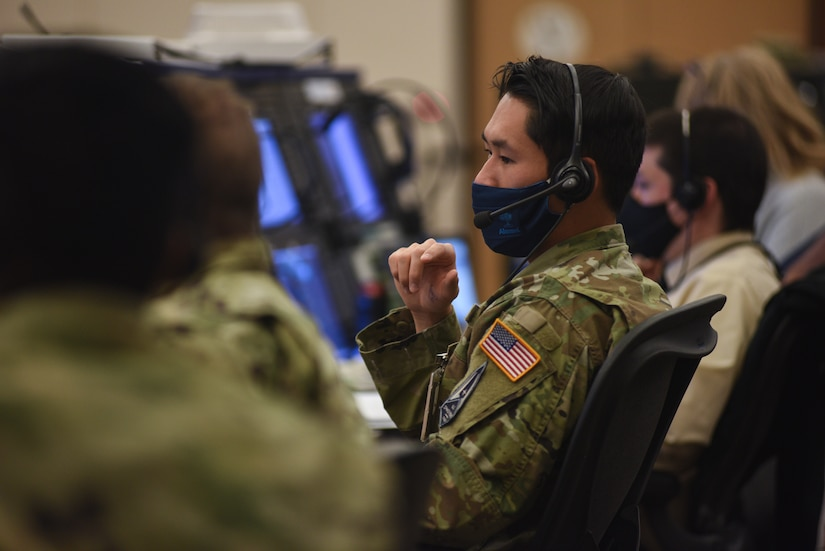 A row of people wearing headsets and face masks sit at desks and look at computer screens.
