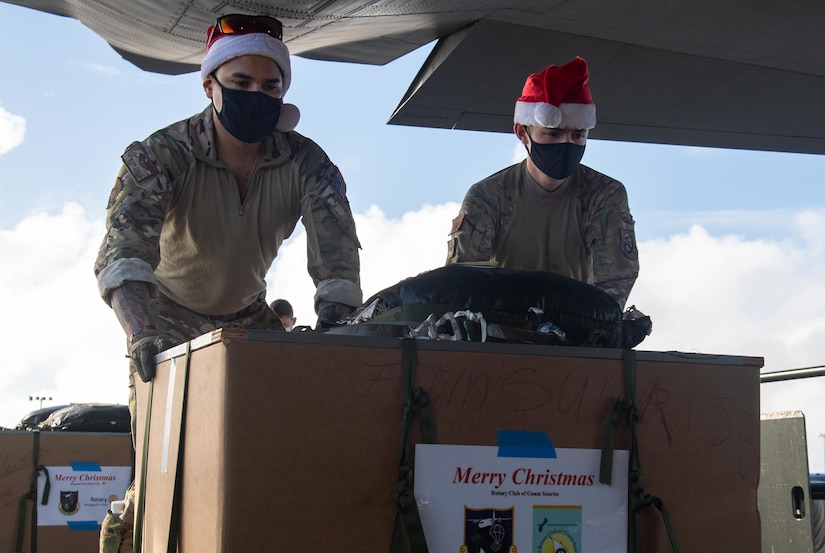 Two service members wearing Santa hats load a large box into a plane.