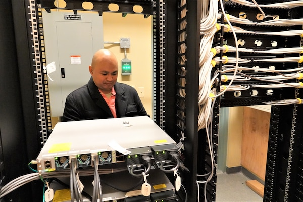 Aaron Aguilar, Information Technology Specialist/Telecommunication Officer works in one of the District's telecommunications rooms.