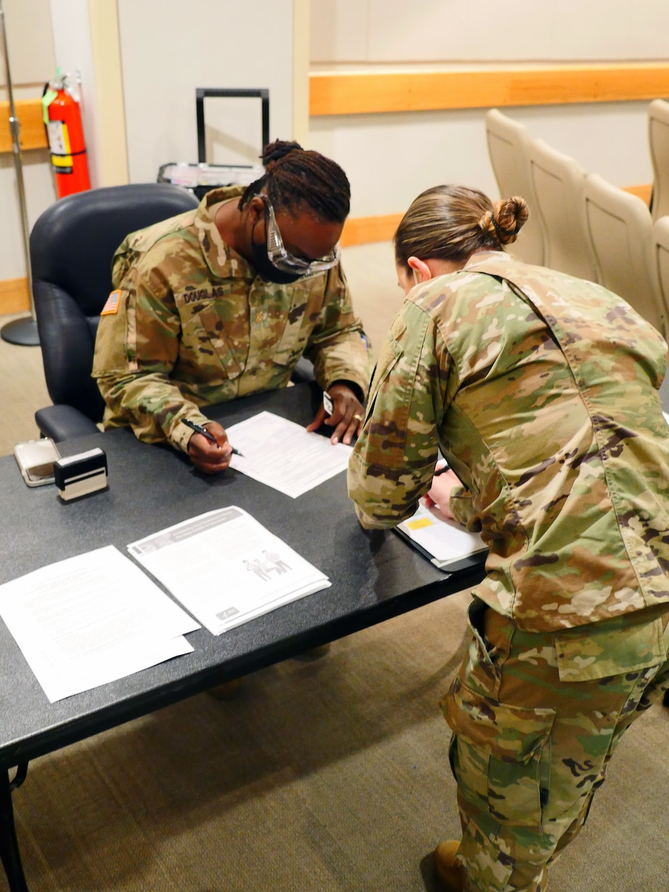 Soldiers complete paperwork on a desk.