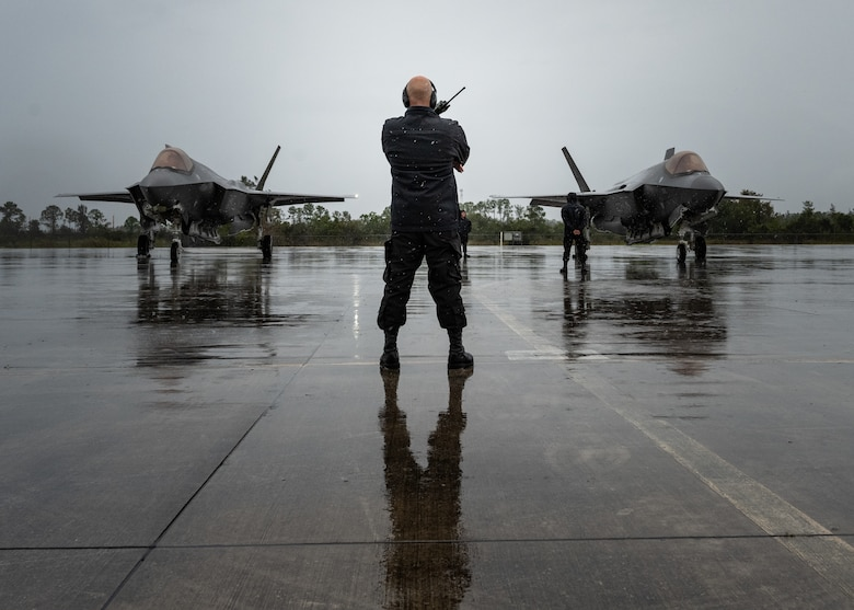 An F-35A Demonstration Team Maintainer stands before two F-35A Lightning IIs prior to take-off.