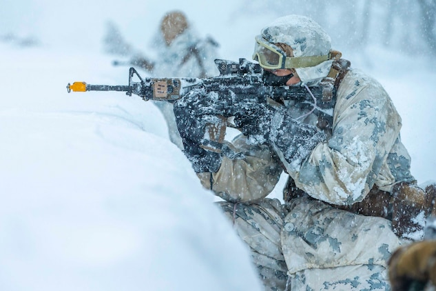 A Marine looks through the scope of a weapon while kneeling behind a mound of snow.