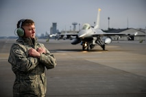 U.S. Air Force Airman Corey Tidwell, a 35th LRS fuels distribution journeyman, prepares to marshal an F-16 Fighting Falcon during Agile Combat Employment week at Misawa Air Base, Japan, Dec. 10, 2020. The 35th LRS tested a new cargo deployment function (CDF) process that centralized representatives from all units and their unpacked cargo in one location to collectively pack individual storage units, reducing the CDF timeline and deployment footprint. (U.S. Air Force photo by Airman 1st Class China M. Shock)