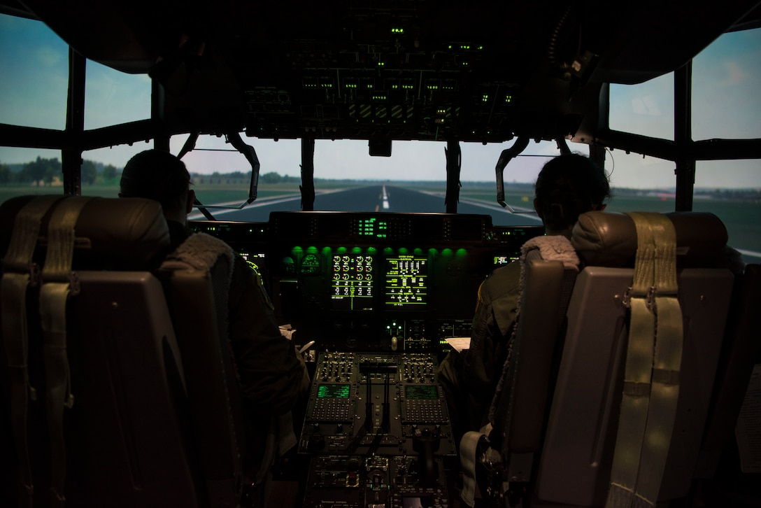 Two people in the cockpit of a C-130 simulator.