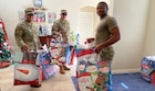 Three men in military uniform carry Christmas bags