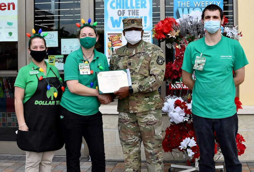 A man in military uniform presents a certificate to three store employees