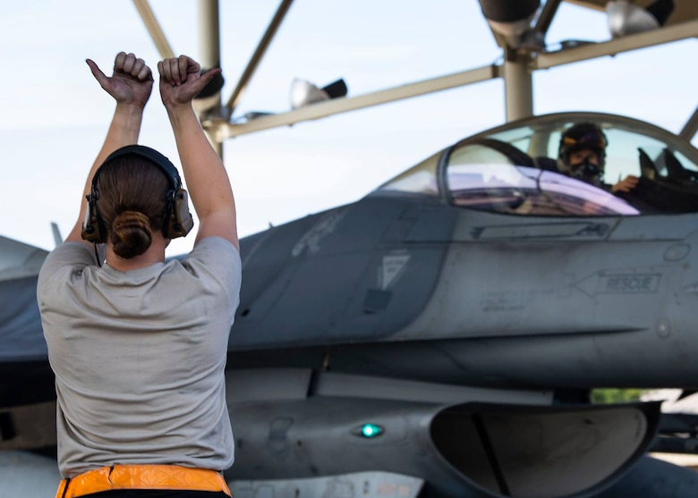 Airman marshals a jet