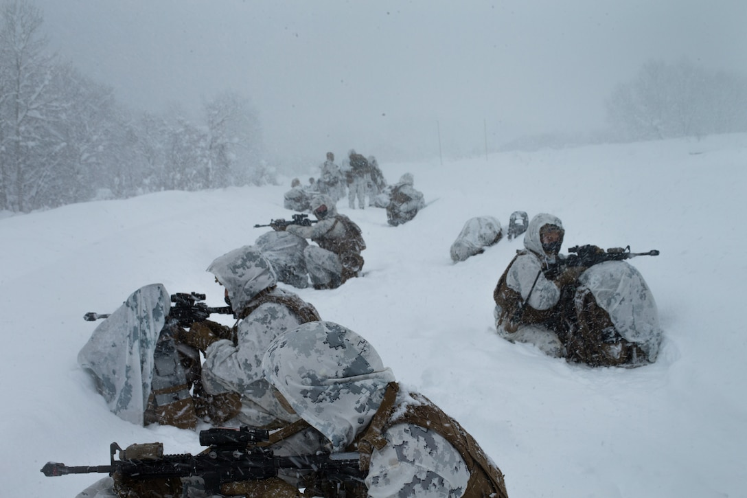 Marines with guns sit in the snow.