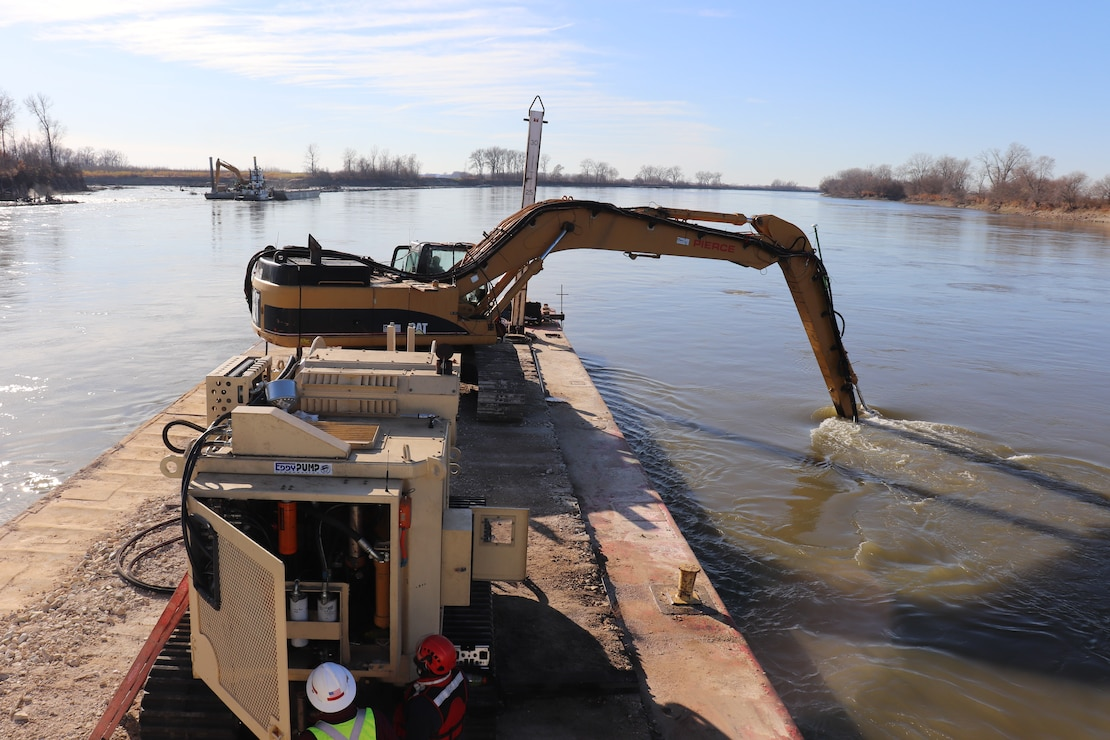 A Kansas City District track-hoe on a barge work boat took part in hydrodynamic dredging operations on the Missouri River November 11, 2020. The hydrodynamic dredge head is mounted on the bucket and the arm directs the flow the desired area of concern to be affected. The Engineering Research and Development Center brought the system to Kansas City District from Vicksburg, Miss., to assist in clearing shoals that developed on the Missouri River due to damages from flooding to the river control structures. The device enabled the combined team to redirect sandy material back into suspension in the current of the river and away from the built-up areas that impede navigation on the river.