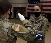 Cadet Haley Kieny, left, salutes Cadet Hannah Minns after presenting her a folded American flag during military funeral honors practice at Camp Johnson, Vermont, Dec. 18, 2020. The 40-hour Honor Guard course trains Soldiers how to conduct color guards, funeral honors and other ceremonies. The cadets are assigned to the University of Vermont-Montpelier Army ROTC. (U.S. Army National Guard photo by Don Branum)