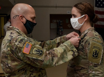 Maj. Jason Beams presents Cadet Hannah Minns with an Army Achievement Medal during a recognition ceremony at Camp Johnson, Vermont, Dec. 18, 2020. Minnis, a cadet with University of Vermont ROTC, received a perfect score in the Vermont Army National Guard's Military Funeral Honors training, a 40-hour course that prepares Soldiers to render services for funerals, color guards, and other formal ceremonies. Beans is the Vermont National Guard liaison and operations officer for the UVM ROTC Program. (U.S. Army National Guard photo by Don Branum)