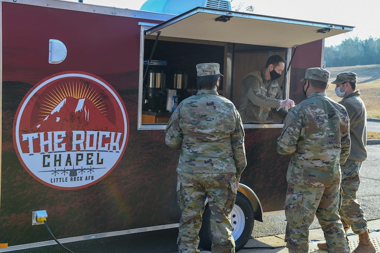 a man gives coffee to airmen