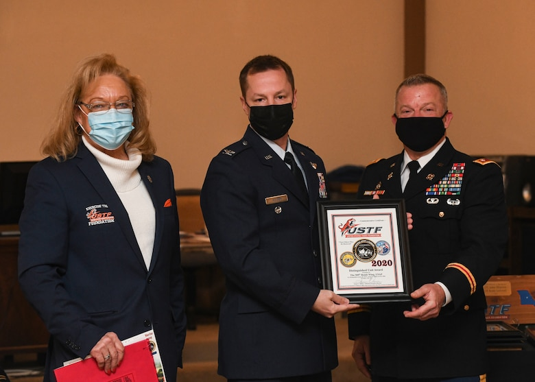 Susan Haines, Exercise Tiger Association national executive director, U.S. Air Force Col. Kyle J. Wilson, 509th Bomb Wing vice commander, and U.S. Army Maj. Gen. Levon E. Cumpton, Missouri National Guard Adjutant General, pose with an Annual Adopt A Warrior award plaque, at Columbia, Missouri, Dec. 12, 2020. The event displayed the close bonds between Team Whiteman and the local Columbia community. Following the ceremony, service members participating in the event received USTF specific medals and were recognized during a football game for their outstanding achievements and meritorious service. (U.S. Air Force photo by Staff Sgt. Sadie Colbert)