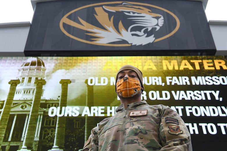 U.S. Air Force Tech. Sgt. Justin Stinson, 393rd Bomb Squadron superintendent, stands in front of a JumboTron at the University of Missouri, Columbia, Missouri, Dec. 12, 2020. Team Whiteman personnel attended the game to participate in the 22nd Annual Adopt A Warrior military recognition. The Exercise Tiger Association host the annual event to show honor and appreciation for service members' sacrifice and to recognize the militaries outstanding achievements and meritorious service to U.S. and its allies. (U.S. Air Force photo by Staff Sgt. Sadie Colbert)
