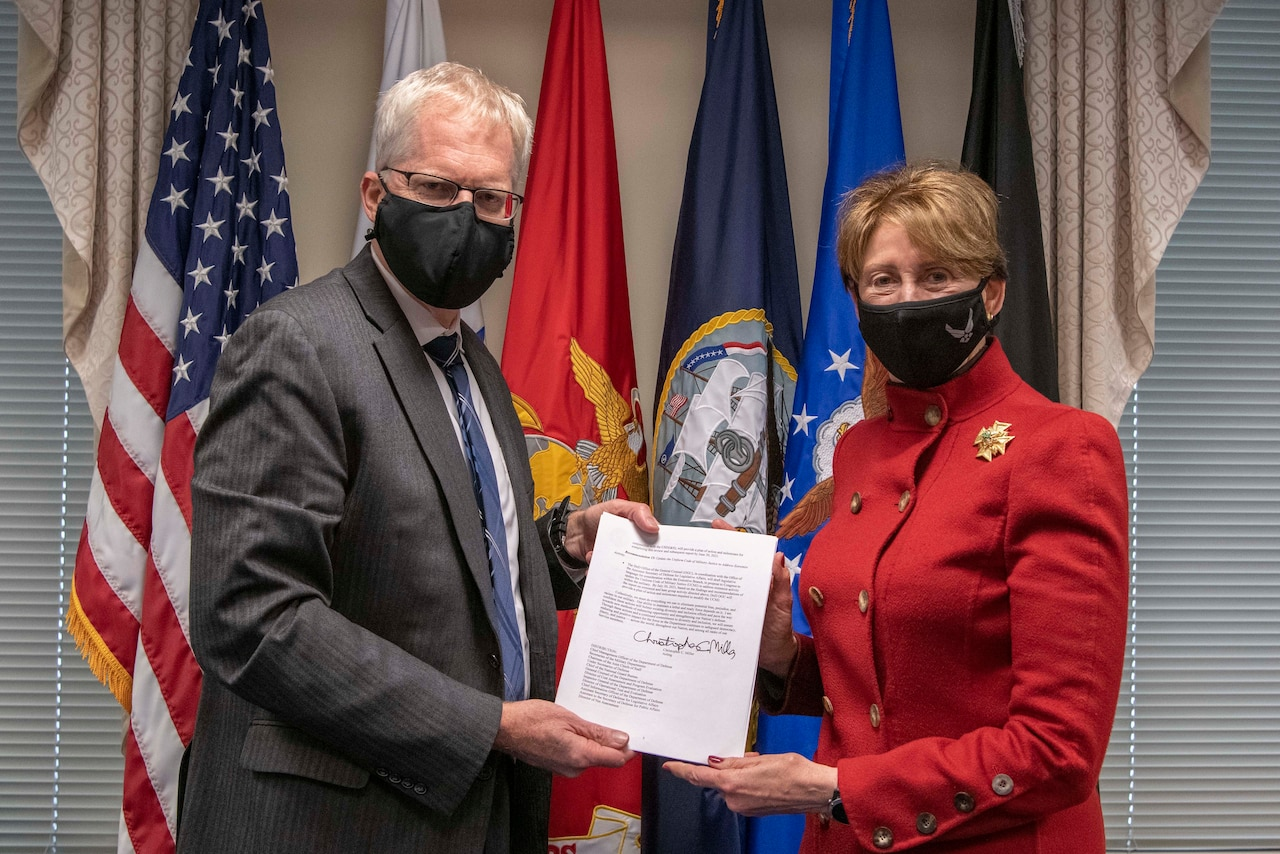 A man and a woman pose with a signed document.