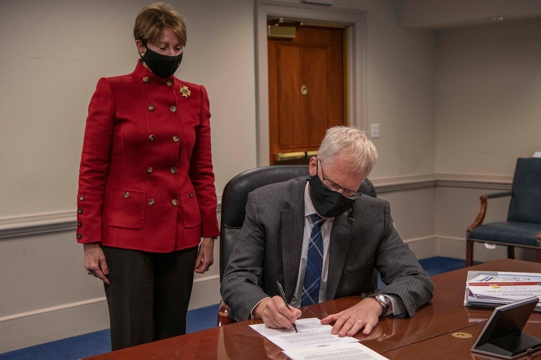 A man signs a document while a woman watches.