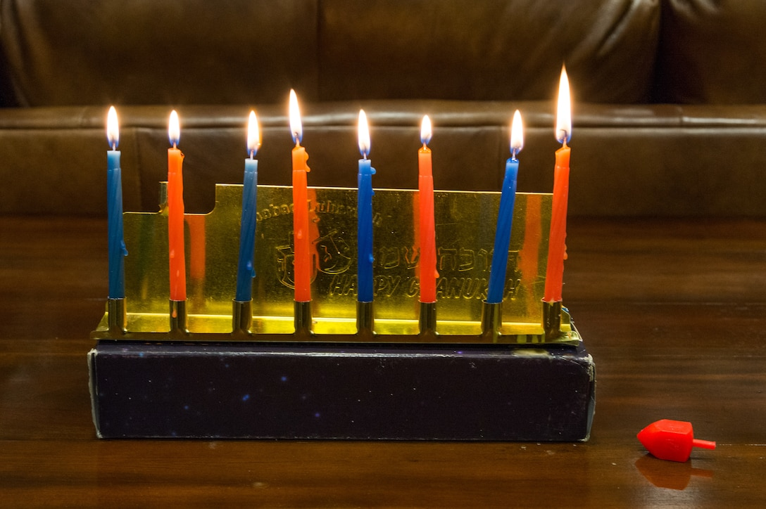 A menorah with eight lit candles and a dreidel are displayed on the evening of Dec. 17, 2020, at Dover Air Force Base, Delaware. The lighting of the first candle on a menorah started on the evening of Dec 10., with the eighth candle being lit on the evening of Dec. 17. Hanukkah ends the evening of Dec. 18. (U.S. Air Force photo by Roland Balik)