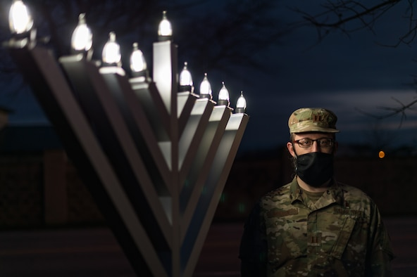Capt. Levi Welton, 436th Airlift Wing chaplain, lights the Dover Air Force Base menorah Dec. 17, 2020, at Dover Air Force Base, Delaware. Hanukkah, started with the lighting of the first menorah candle the evening of Dec 10. and ends with the eighth candle being lit on the evening of Dec. 17. Hanukkah concluded on the evening of Dec. 18. (U.S. Air Force photo by Roland Balik)