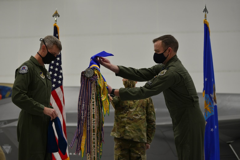 U.S. Air Force Lt. Col. Samuel Chipman unveils the 355th Fighter Squadron guidon during a reactivation ceremony at Eielson Air Force Base, Alaska, Dec. 18, 2020.