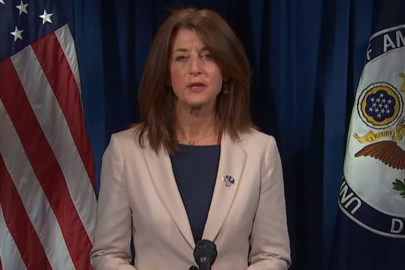 A woman flanked by a flag and a seal looks forward.