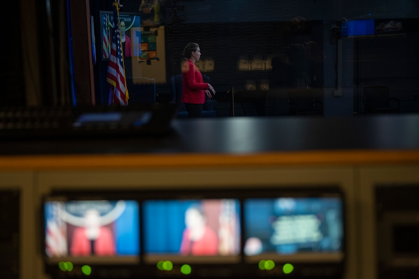 A  woman stands in the background of a row of three video monitors.