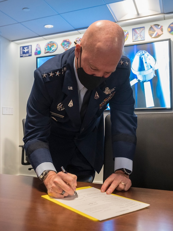 General John Raymond, Chief of Space Operations, U.S. Space Force, signs a document officially transferring U.S. Air Force Colonel, and NASA astronaut, Mike Hopkins to the U.S. Space Force, Friday, Dec. 18, 2020, from the Space Operations Center at NASA Headquarters in Washington