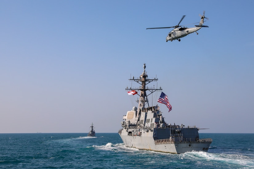 Royal Saudi Naval Force corvette HMS Badr (612), left, and the guided-missile destroyer USS Winston S. Churchill (DDG 81) transit the Arabian Gulf with a U.S. Navy MH-60R Sea Hawk helicopter during a joint and combined air operations in support of maritime surface warfare (AOMSW) exercise in the Arabian Gulf, Dec. 18. Combined integration operations between joint U.S. forces are regularly held to maintain interoperability and the capability to counter threats posed in the maritime domain, ensuring freedom of navigation and free flow of commerce throughout the region's heavily trafficked waterways.