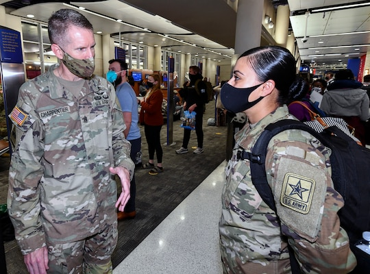 Command Sgt. Maj Clark Charpentier, U.S. Army Medical Center of Excellence, talks with Spc. Jasmine Lewis, a 68C Practical Nursing Specialist trainee assigned to MEDCoE as she awaits travel to Connecticut on Holiday Block Leave at the San Antonio International Airport Dec. 19.