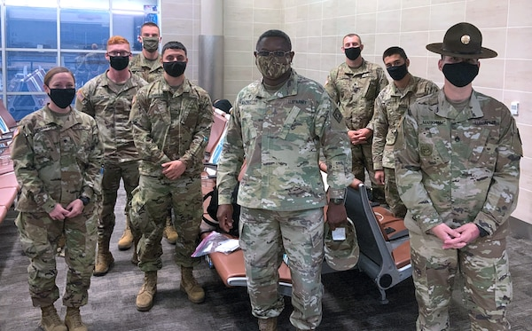 Drill Sergeant Jeffrey Markham (far right) and Chaplain (Maj.) Oyedeji Idowu (center) speak with Soldiers in training at the U.S. Army Medical Center of Excellence as they await flights from the San Antonio International Airport for Holiday Block Leave Dec. 19.