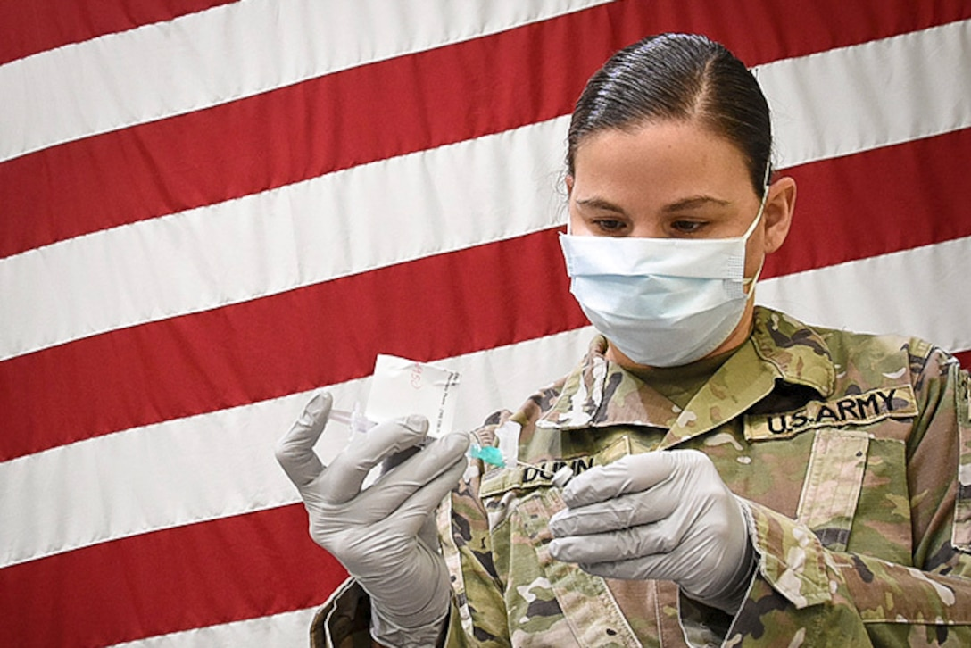 A soldier wearing gloves and face mask holds a vial and a syringe while standing in front of an American flag.