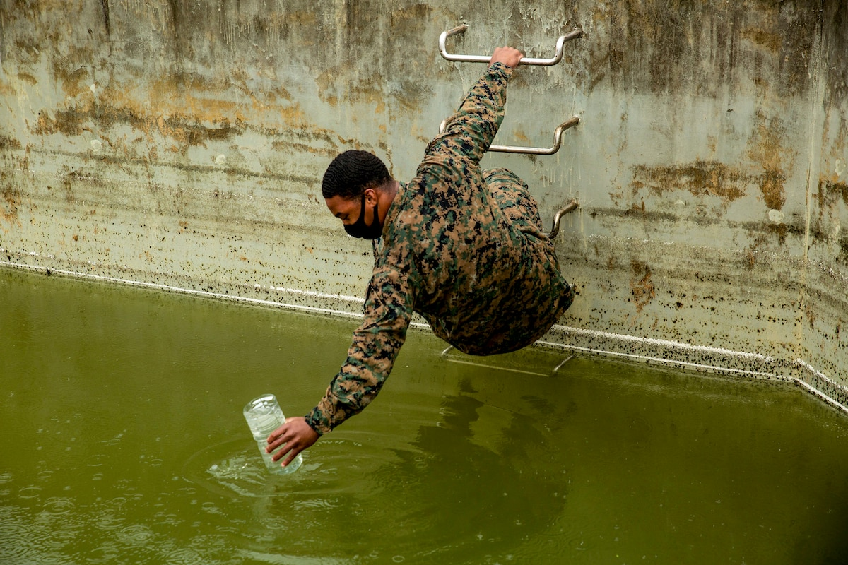 A Marine holds onto a ladder with one hand and reaches a cup into a pool of green water beneath him with the other.