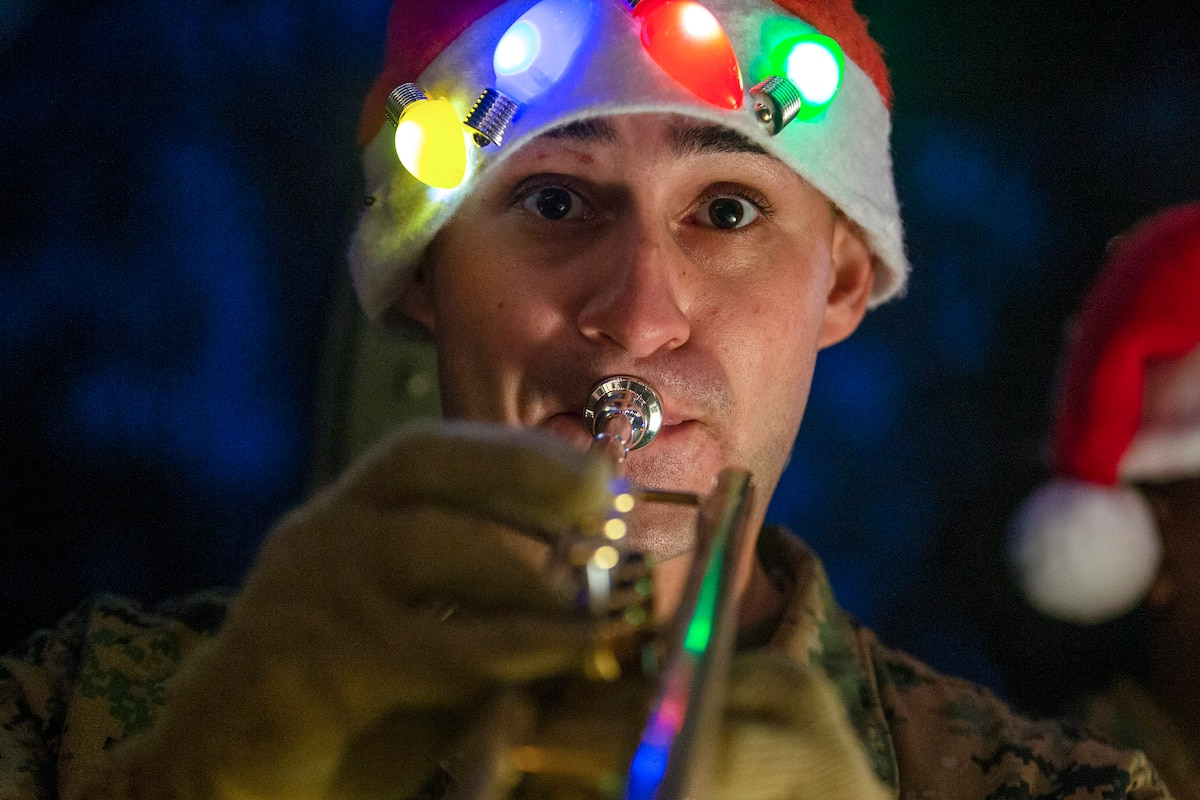 A Marine wearing a Santa hat with Christmas lights on it plays a trumpet.