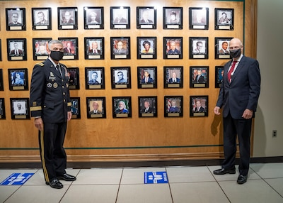 GEN Paul M. Nakasone, Commander, U.S. Cyber Command, Director, NSA/Chief CSS, (left) and George Barnes, NSA Deputy Director, (right) stand for a photo near the portraits of this year's inductees into the NSA/CSS Cryptologic Hall of Honor
