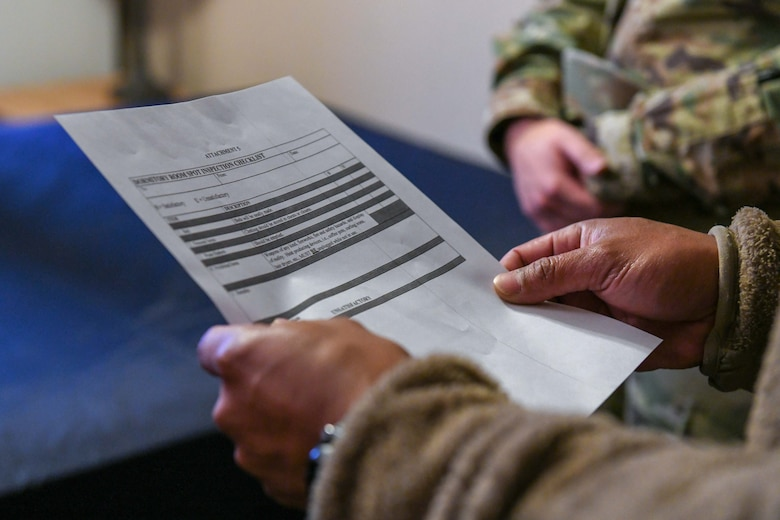 An Airman looks at a piece of paper.