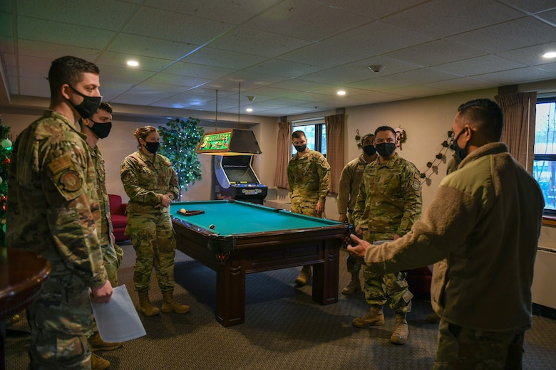 Airmen stand around a pool table discussing an ALS course.