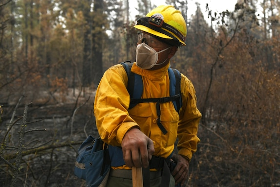 As the year would prove to be a record-breaking one for massive wildfires raging throughout the West, National Guard members were activated to help augment firefighters. Here, Chief Master Sgt. Daniel Garvida, an engineer superintendent with the Washington Air National Guard's 194th Wing, sizes up the next challenge of a wildfire fight near Inchelium, Washington, Sept 16. Garvida as well as 14 other Air National Guard members from the 194th Wing and 225th Air Defense Group spent 10 days fighting fires in Eastern Washington. (Air National Guard photo by Master Sgt. Tim Chacon)