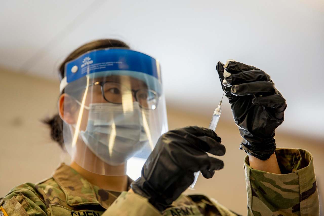 A soldier wearing a mask holds the COVID-19 vaccine.