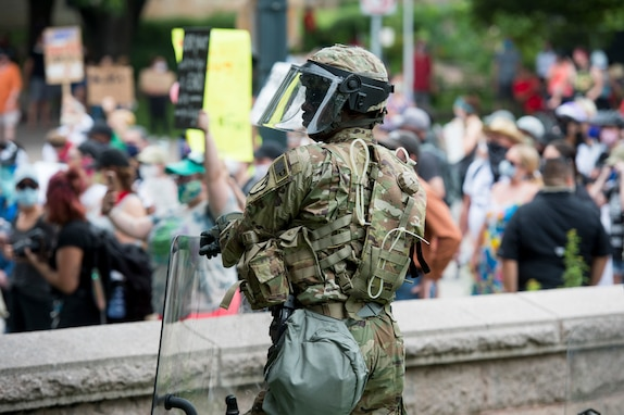 A Soldier with the Texas Army National Guard's 136th Maneuver Enhancement Brigade stands guard during a protest in Austin, Texas, May 31. The Texas National Guard augmented law enforcement agencies throughout the state to protect critical infrastructure while safeguarding Texans' First Amendment right to peacefully protest. (U.S. Army National Guard photo by Charles E. Spirtos)