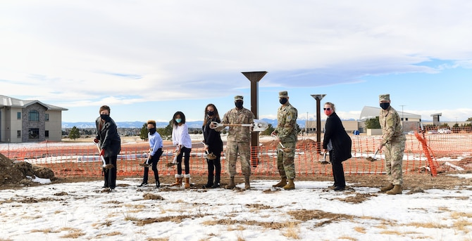 From left to right, Debbie Southee, 460th Force Support Squadron civilian leader, Luke and Madi Pepper, Alicia Pepper, Col. Devin Pepper, Buckley Garrison commander, Chief Master Sgt. Robert Devall, BGAR command chief, Jenny Meadlin, 460th Contracting Squadron contracting officer, and Col. Brian Chellgren, 460th Mission Support Group commander, dig their shovels into the soil outside of the construction site for Buckley Garrison's Community Playground near Rocky Mountain Lodge during the groundbreaking ceremony on Buckley Air Force Base, Co., Dec. 21, 2020.