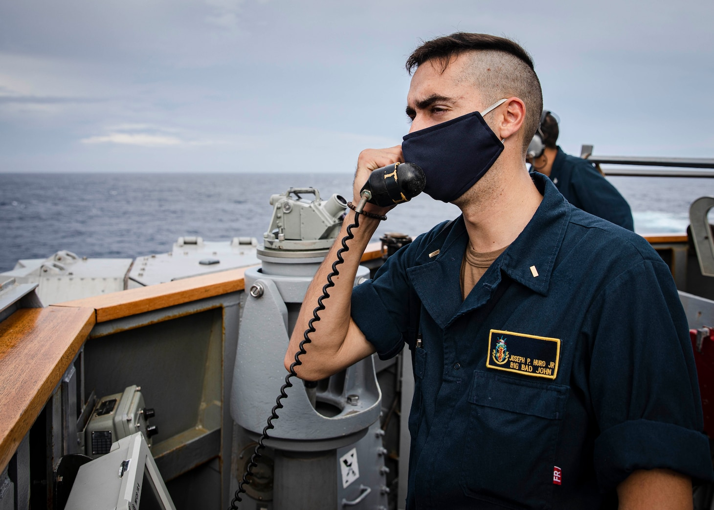 SOUTH CHINA SEA (Dec. 22, 2020) Conning Officer Ensign Joseph Hurd, from Foley, Alabama, gives course and speed orders to the helm while standing watch on the bridge wing as the guided-missile destroyer USS John S. McCain (DDG 56) conducts routine underway operations. McCain is forward-deployed to the U.S. 7th Fleet area of operations in support of security and stability in the Indo-Pacific region. (U.S. Navy photo by Mass Communication Specialist 2nd Class Markus Castaneda)