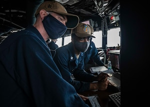 SOUTH CHINA SEA (Dec. 22, 2020) Navigator Lt. j.g. Daniel Feeney, left, from Old Greenwich, Connecticut, and Quartermaster 2nd Class Asah Favors, from Suffolk, Virginia, review the ship's course on the voyage management system (VMS) while standing watch in the pilot house as the guided-missile destroyer USS John S. McCain (DDG 56) conducts routine underway operations. McCain is forward-deployed to the U.S. 7th Fleet area of operations in support of security and stability in the Indo-Pacific region. (U.S. Navy photo by Mass Communication Specialist 2nd Class Markus Castaneda)
