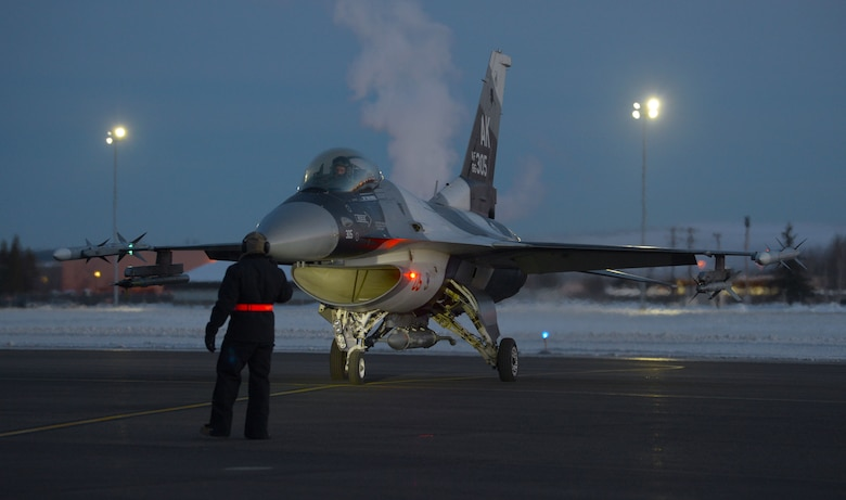A U.S. Air Force Airman assigned to the 354th Maintenance Group inspects a U.S. Air Force F-16 Fighting Falcon intake for ice build up prior to launch for an elephant walk on Eielson Air Force Base, Alaska, Dec. 18, 2020.