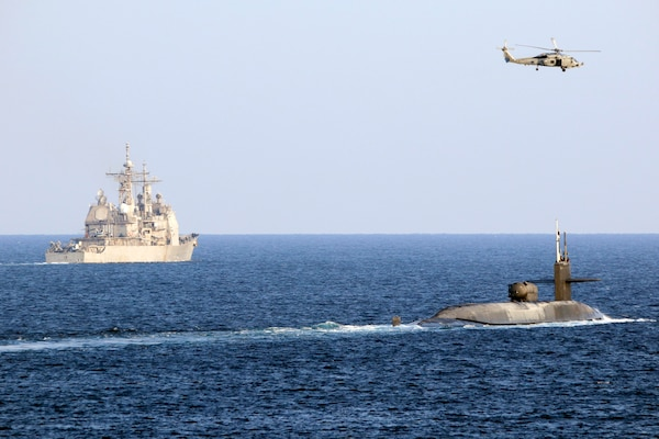 The guided-missile submarine USS Georgia (SSGN 729), right, transits the Strait of Hormuz with the guided-missile cruiser USS Port Royal (CG 73), the guided-missile cruiser USS Philippine Sea (CG 58), not pictured, and a MH-60R Sea Hawk helicopter, attached to Helicopter Maritime Strike Squadron (HSM) 48, Dec. 21. Georgia is deployed to the U.S. 5th Fleet area of operations in support of naval operations to ensure maritime stability and security in the Central Region, connecting the Mediterranean and Pacific through the Western Indian Ocean and three critical chokepoints to the free flow of global commerce.