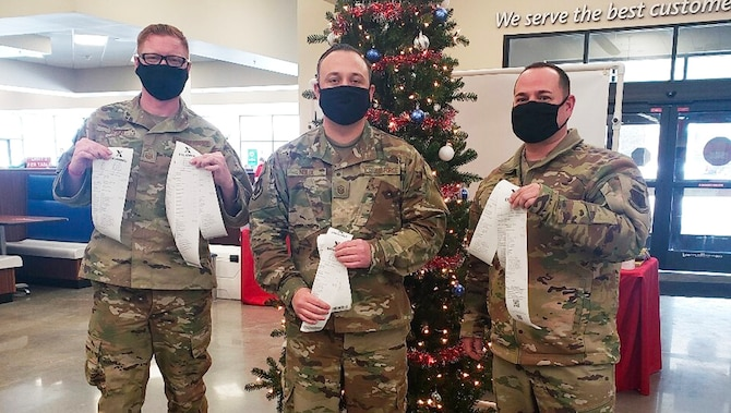 Three first sergeants stand in front of a Christmas tree holding up receipts they received from paying off layaways.